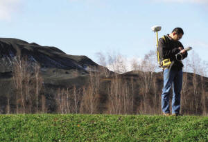 A levee inspector stands on a levee while taking notes.